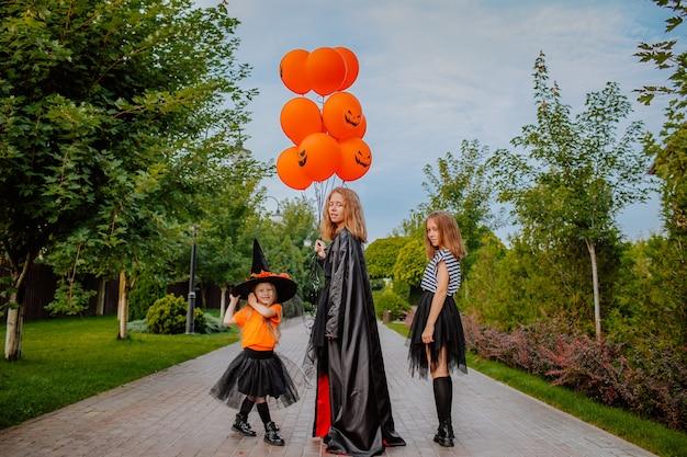 Drie jonge mooie zussen in halloween-kostuums zoals heksen die op straat lopen met een bos ballonnen. vakantieconcept.