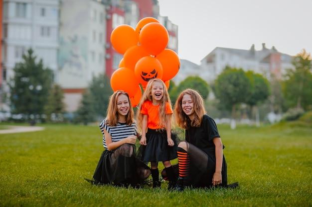 Drie jonge mooie zussen in halloween-kostuums zoals heksen poseren op de open plek met ballonnen. vakantieconcept.