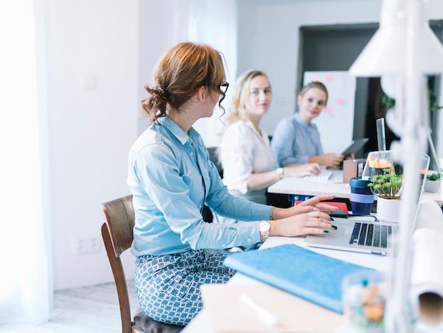 Drie jonge onderneemsters die in bureau spreken