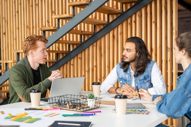 Drie jonge opgeleide ontwikkelaars van software bespreken hun ideeën en nieuw project per tafel