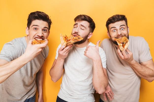 Drie jonge opgetogen mannen die pizza eten