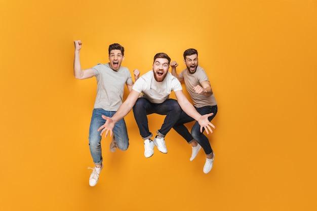 Drie jonge opgewonden mannen die samen springen