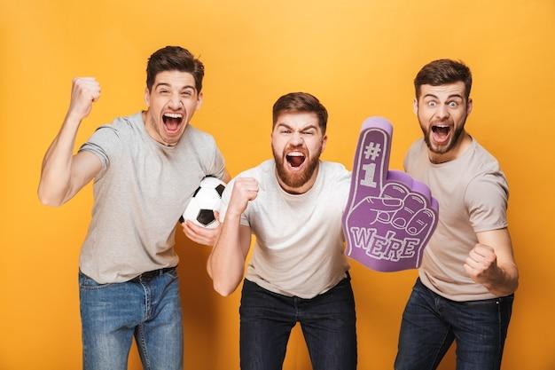 Drie jonge opgewonden mannen voetbalfans vieren
