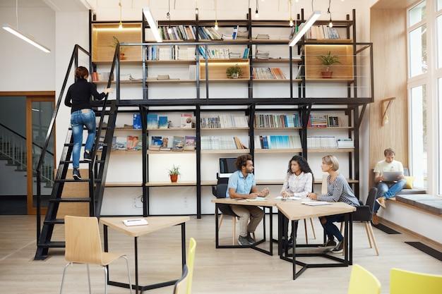Drie jonge perspectief-starters zitten in een moderne lichtbibliotheek tijdens een vergadering, praten over een nieuw project, kijken door de details van het werk, hebben een productieve dag in de atmosfeer van vrienden,