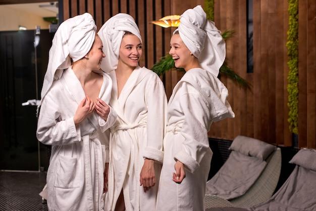 Drie jonge schattige vriendinnen die praten en plezier hebben, ontspannen na spa-procedures