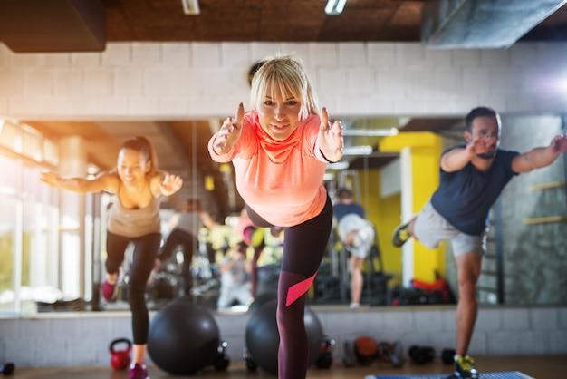 Drie jonge sportieve mensen werken aan hun evenwichtsvaardigheden terwijl ze op één been staan met gestrekte handen voor zich.