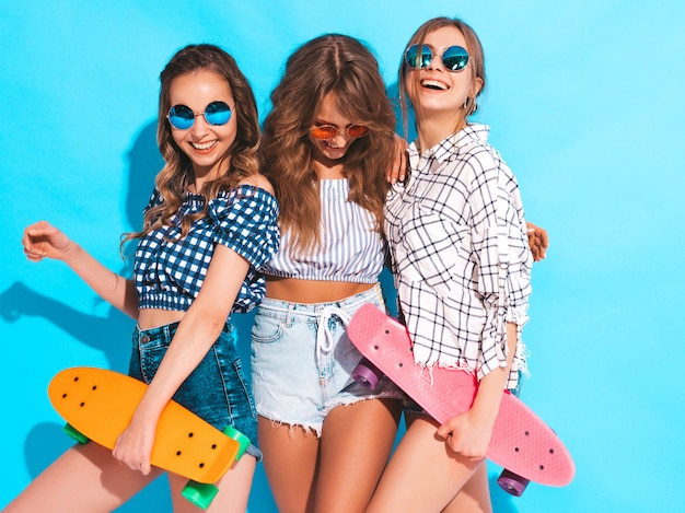 Drie jonge stijlvolle lachende mooie meisjes met kleurrijke penny skateboards. vrouw in de zomer geruit hemd kleren poseren. positieve modellen hebben plezier