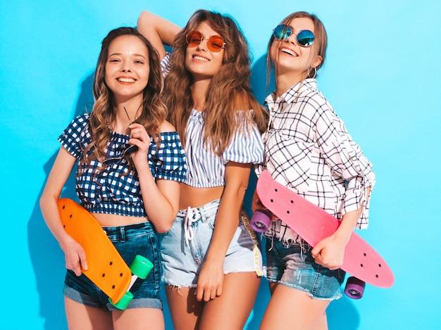 Drie jonge stijlvolle lachende mooie meisjes met kleurrijke penny skateboards. vrouwen in zomer kleding poseren in zonnebril. positieve modellen hebben plezier