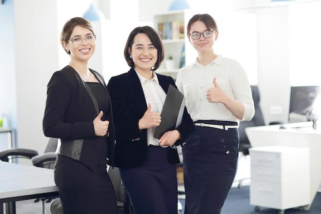 Drie jonge succesvolle zakenvrouwen op kantoor die vrolijk glimlachen