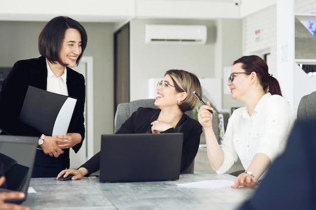 Drie jonge succesvolle zakenvrouwen op kantoor werken samen graag aan een project