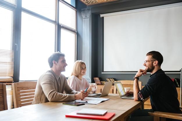 Drie jonge tevreden collega's coworking
