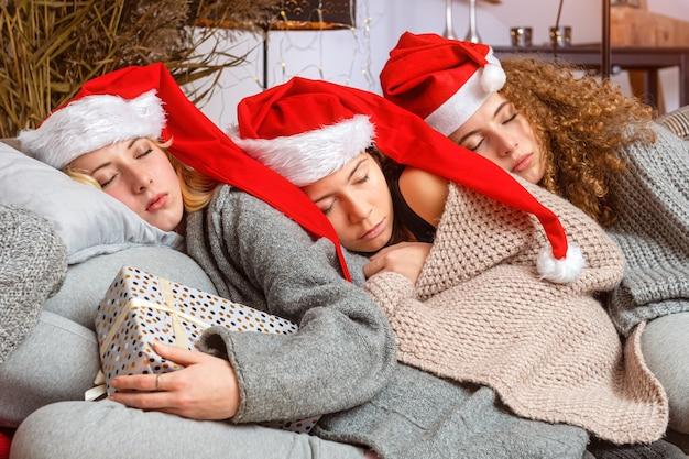 Drie jonge tienermeisjes in rode kerstmutsen vielen in slaap op de bank na het inpakken van kerstcadeautjes