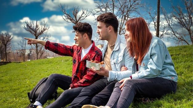 Drie jonge vrienden die op het gras zitten en voedsel in een park houden
