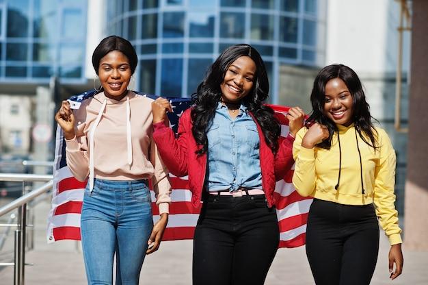 Drie jonge vrienden van de universiteits afrikaanse amerikaanse dames met vlag van de v.s.