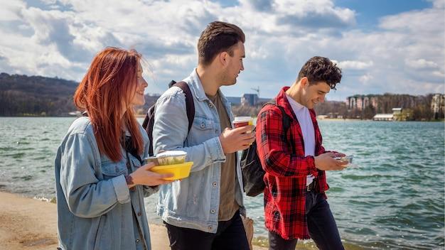 Drie jonge vrienden wandelen langs het meer, drinken en eten in een park