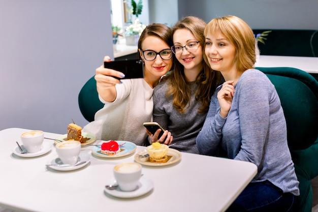 Drie jonge vriendenvrouwen - drie meisjes, zittend aan een tafel in een café, chatten, glimlachen, koffie drinken uit witte bekers, desserts eten, selfies nemen. lifestyle, casual, plezier in communicatie.
