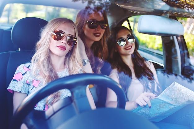 Drie jonge vriendinnen die in een auto reizen