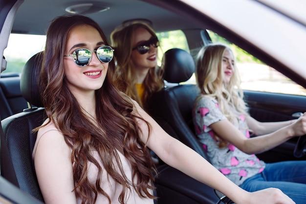 Drie jonge vriendinnen reizen in een auto