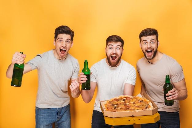 Drie jonge vrolijke mannen die een grote pizza houden