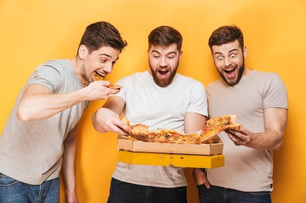 Drie jonge vrolijke mannen die grote pizza eten