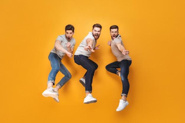 Drie jonge vrolijke mannen die samen springen