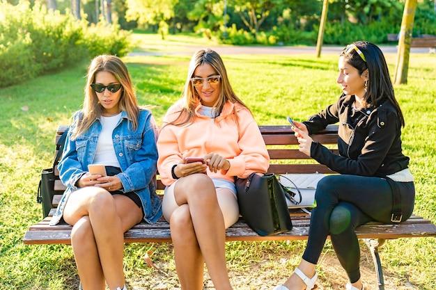 Drie jonge vrouw beste vrienden zittend op een bankje in het stadspark bij zonsondergang of zonsopgang met behulp van de telefoon om berichten met andere vrienden. nieuwe relaties in de moderne tijd. meisjes die plezier hebben met smartphone