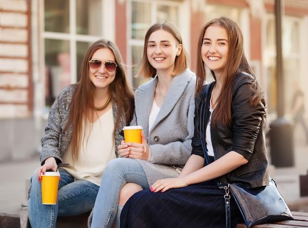 Drie jonge vrouwen, beste vrienden die bij de camera glimlachen