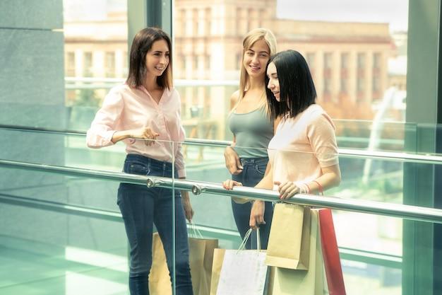 Drie jonge vrouwen bij het winkelen in het wandelgalerij tegen de achtergrond van cit