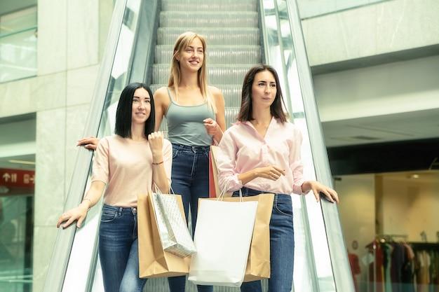Drie jonge vrouwen bij het winkelen in het wandelgalerij