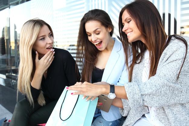 Drie jonge vrouwen delen hun nieuwe aankopen met elkaar en hebben een koffiepauze na het shoppen