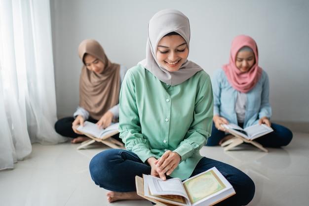 Drie jonge vrouwen die hijabs dragen, lezen het heilige boek van de koran