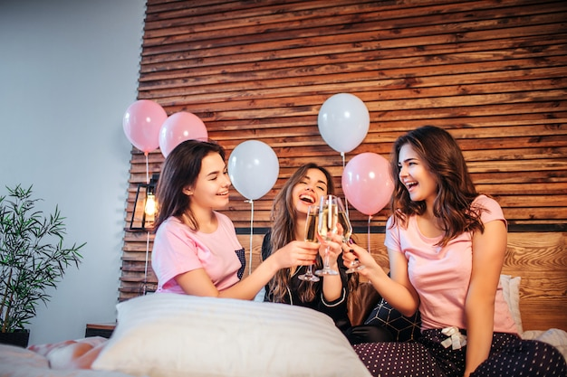 Drie jonge vrouwen hebben pyjamafeestjes in de kamer op bed. ze zitten samen en juichen met glazen champaigne. vrouwen glimlachen. ze zien er gelukkig uit.