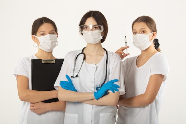 Drie jonge vrouwen in medische kleding op een witte achtergrond