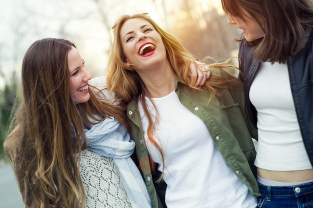 Drie jonge vrouwen praten en lachen in de straat.