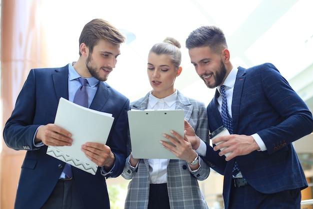 Drie jonge zakenlieden die zaken bespreken tijdens een kantoorvergadering.