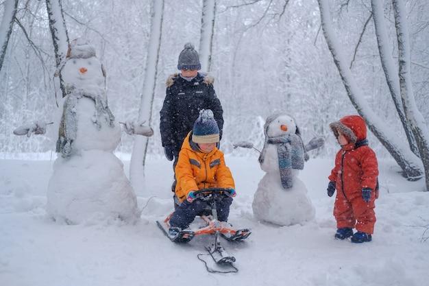 Drie jongens uit dezelfde familie tijdens een wandeling in winterpark en twee grappige sneeuwmannen