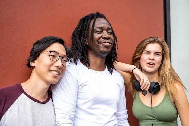 Drie jongeren van verschillende etnische groepen staan naast een muur