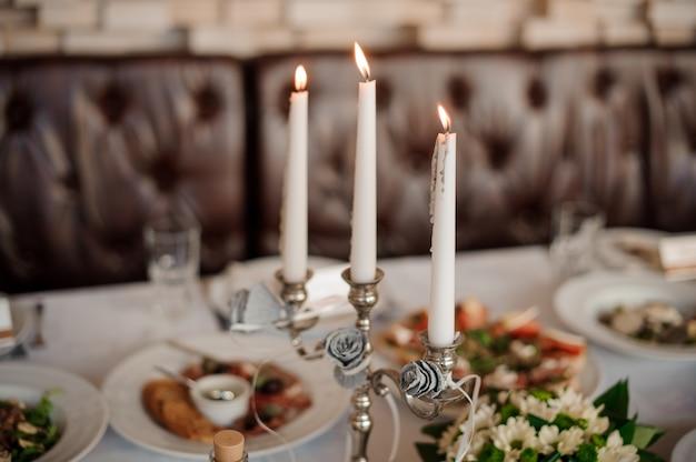 Drie kaarsen in de elegante kandelaar die een tafel versieren