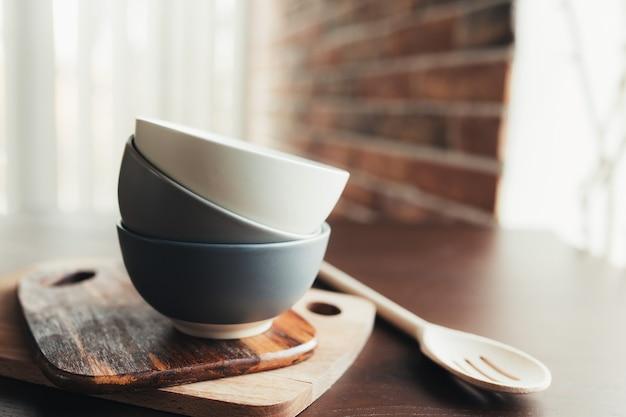 Drie keramische kommen, houten lepel op een houten bruine tafel. onscherpe achtergrond. hoge kwaliteit foto