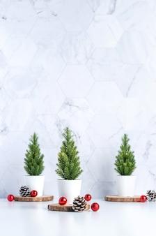 Drie kerstboom met dennenappel en decor xmas bal op witte tafel en marmeren tegelmuur