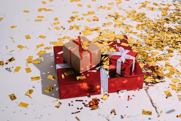 Drie kerstcadeaus van verschillende grootte verpakt in inpakpapier en strik en verspreide gouden confetti.