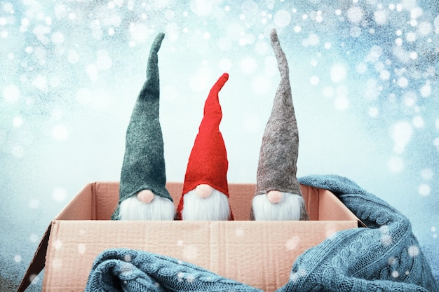 Drie kerstkabouters van verschillende kleuren in open doos, gebreide deken