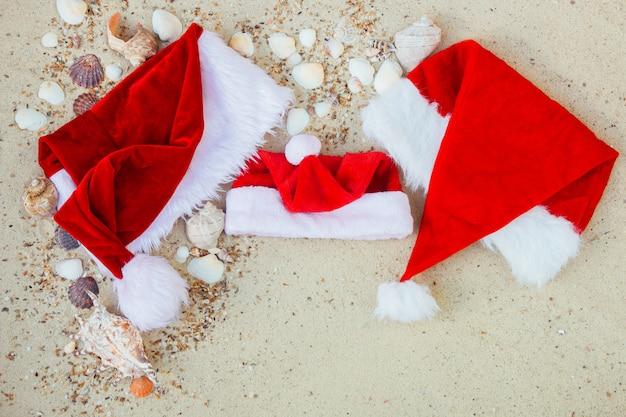 Drie kerstmutsen op het strand kerstmuts op het zand in de buurt van schelpen familie vakantie nieuwjaar vakantie frame