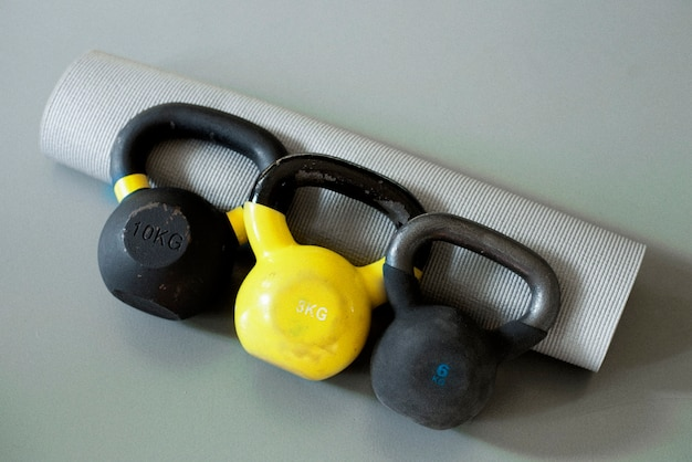 Drie kettlebells en grijze yogamat