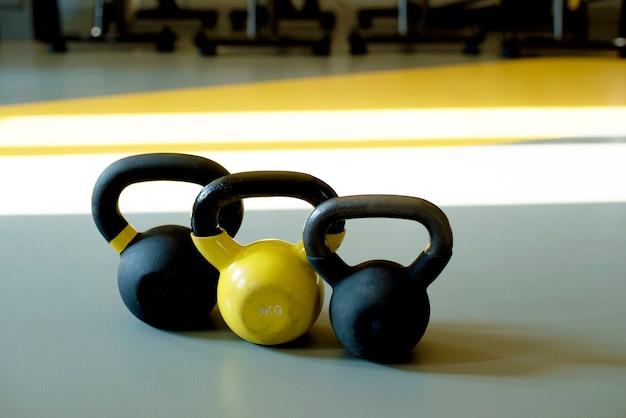 Drie kettlebells staan in een rij op een grijze vloer in een lichte fitnessruimte. gele kettlebell, zwarte kettlebell