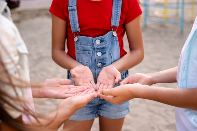 Drie kinderen die hun handen bij elkaar houden