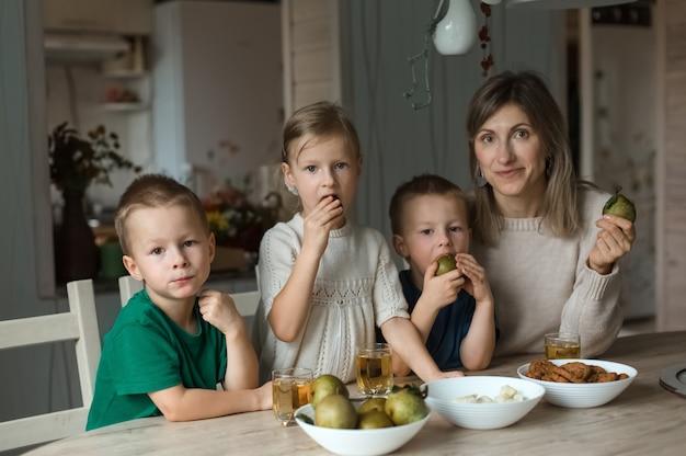 Drie kinderen en moeder, een gezin, zitten aan een tafel met fruit. hoge kwaliteit foto