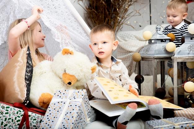 Drie kinderen kinderen zitten tussen kerst geschenkdozen in een versierd huis. prettige kerstdagen en fijne feestdagen!