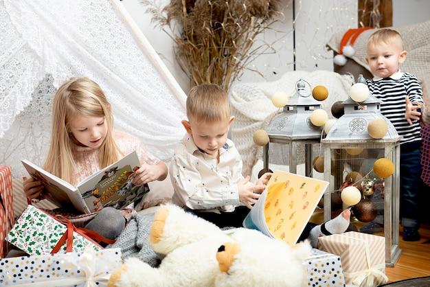 Drie kinderen lezen boeken tussen kerstgeschenkdozen in een versierd huis. prettige kerstdagen en fijne feestdagen!