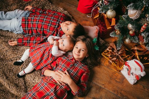 Drie kinderen liggen naast een kerstboom